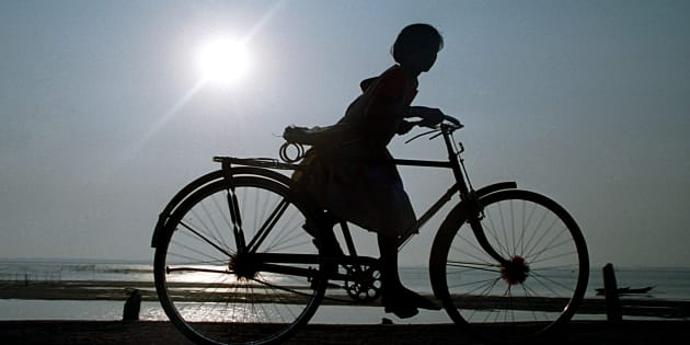 Girl riding bicycle, Delhi, India. (Photo by: IndiaPictures/UIG via Getty Images)