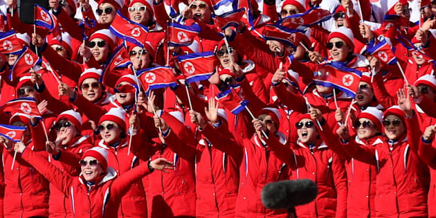 North Korean cheerleaders wave their flag as they watch their national skier compete in the Women's Slalom at the Jeongseon Alpine Center during the Pyeongchang 2018 Winter Olympic Games in Pyeongchang on February 16, 2018. / AFP PHOTO / Roberto SCHMIDT        (Photo credit should read ROBERTO SCHMIDT/AFP/Getty Images)