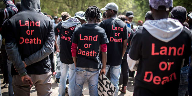 Members of Black First Land First (BLF) wear shirts with the text 'Land or Death' as they prepare to march to the offices of KPMG on Thursday in Johannesburg.
