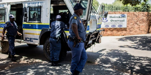 South African Police officers outside Hoërskool Overvaal during a protest.