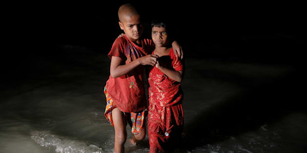 Rohingya refugee sisters, who just arrived under the cover of darkness by wooden boats from Myanmar, hug each other as they try to find their parents at Shah Porir Dwip, in Teknaf, near Cox's Bazar in Bangladesh, September 29, 2017. Picture taken September 29, 2017. REUTERS/Damir Sagolj