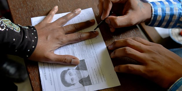 An election official puts indeliable ink on the finger of a voter before she casts her ballot in a file photo.