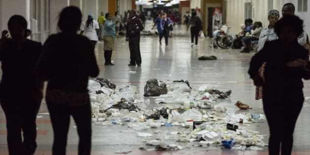 Patients walk through waste and garbage bags at the Charlotte Maxeke Hospital in Johannesburg, during a protest by the employees on May 31 2018.