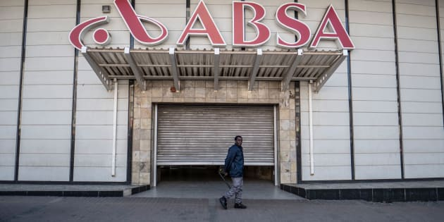 A security official stands at the shuttered entrance to the closed Absa Bank headquarters in Johannesburg on June 28, 2017, as unseen members of the Black First Land First movement (BLF) demonstrate.