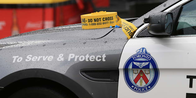 Police tape sits atop a Toronto police car.