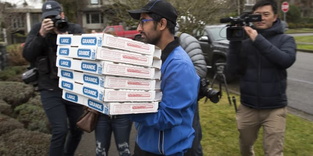 Media photograph a pizza delivery man as he arrives at the residence of Huawei Technologies Chief Financial Officer Meng Wanzhou after she was released on bail in Vancouver, British Columbia on December 12, 2018.