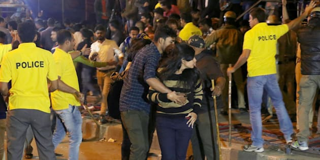 In this photograph taken on January 1, 2017, an Indian man helps a woman (C) leave as police personnel try to manage crowds during New Year's Eve celebrations in Bangalore on January 1, 2017.