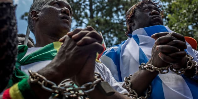 Members of the Africa Diaspora Forum (ADF), civil society organisations, churches, trade unions and other coalitions wear chains and shout slogans during a demonstration against the slave trade and human trafficking in Libya on December 12, 2017 at the Union Buildings in Pretoria.