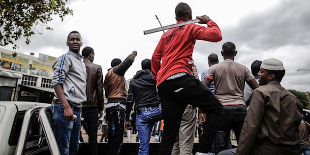 Somali migrants armed with rocks and sticks watch from the back of a pick up truck as a police helicopter hover over an anti-immigration march in the Marabastad neighbourhood in Pretoria on February 24, 2017.
