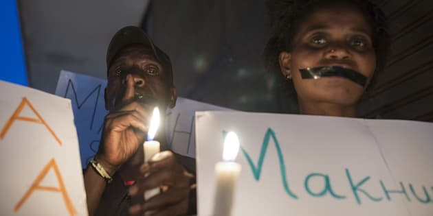 Demonstrators gathered in front of the office of the presidency of Gauteng State hold placards during a protest held over the death of 94 psychiatry patients.