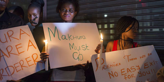 Demonstrators gathered in front of the office of the presidency of Gauteng State hold placards during a protest held over the death of 94 psychiatry patients sent to civil society organization headquarters by the Esidimeni Clinic in Johannesburg due to the high costs of treatment.
