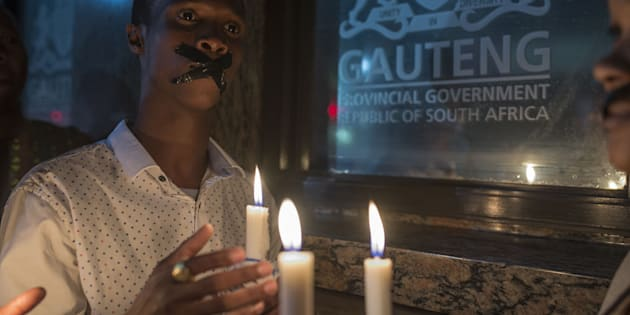 Demonstrators gathered in front of the office of the presidency of Gauteng State hold placards during a protest held over the deaths of more than 140 psychiatric patients.