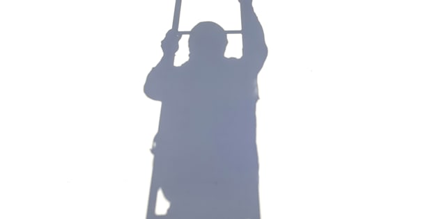 Shadow of worker climbing on ladder isolated on white background.