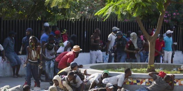 Des protestants se protègent de la police, pendant une manifestation pour demander la démission du président Jovenel Moïse.