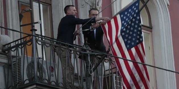 Des employés retirent le drapeau américain du consulat des États-Unis à Saint-Pétersbourg le 31 mars.