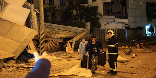 Two guests are escorted by rescue workers from the damaged Marshal Hotel in Hualien, eastern Taiwan early on Feb.  7, 2018, after a strong earthquake struck the island.
