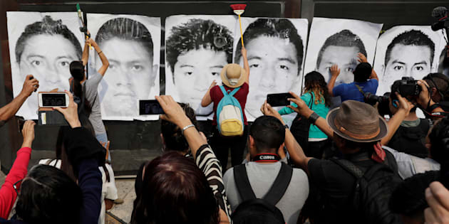 Personas colocan carteles en una pared con imágenes de algunos de los 43 estudiantes desaparecidos del Colegio Ayotzinapa Raúl Isidro Burgos durante una marcha en Ciudad de México, el pasado 26 de abril de 2018.