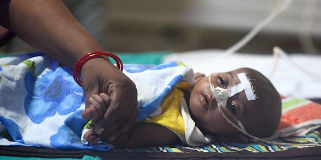An Indian woman holds her child's hand at the encephalitis ward of the the Baba Raghav Das Hospital in Gorakhpur, in the northern Indian state of Uttar Pradesh, on August 14, 2017.