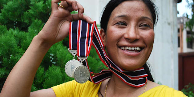 Indian mountaineer and mother of two children, Anshu Jamsenpa holds her medals received from the Nepalese government for summiting Mount Everest twice.