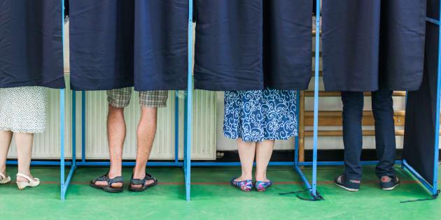 Des votants dans un isoloir.