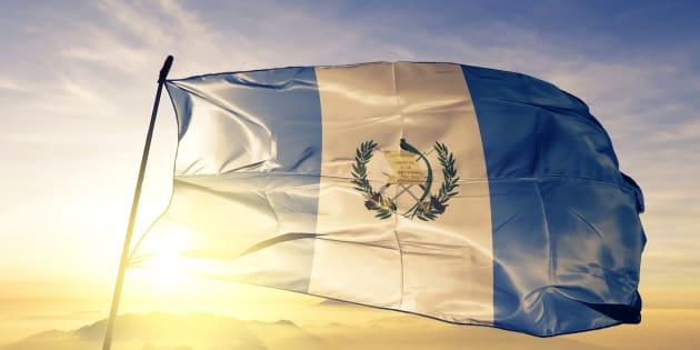 Guatemala Guatemalan Guatemaltec flag on flagpole textile cloth fabric waving on the top sunrise mist fog