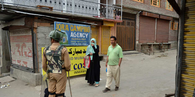 An Indian paramilitary trooper stops a Kashmiri couple during a curfew in Srinagar on July 12, 2016.