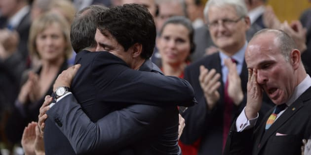 Prime Minister Justin Trudeau hugs Liberal MP Rob Oliphant as MP Randy Boissonnault wipes a tear after making a formal apology in the House of Commons to individuals harmed by federal policies that led to discrimination against LGBTQ2 people in Canada on Nov. 28, 2017.