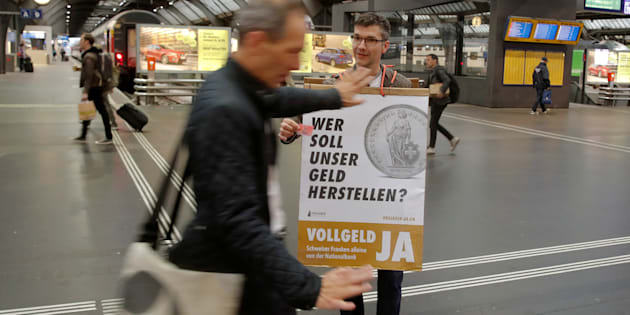 "A member of the sovereign money initiative, a referendum campaign that would abolish traditional bank lending and allow only money created by the Swiss National Bank (SNB), offers flyers to travellers at the central railway station in Zurich, Switzerland May 3, 2018. The poster reads, ""Who should produce our money? Sovereign money yes - Swiss francs from National Bank only"".  REUTERS/Arnd Wiegmann"