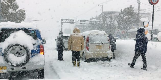 大雪で動けなくなった乗用車とドライバーら=6日午前、福井市内の国道8号※車のナンバーにモザイクをかけてあります