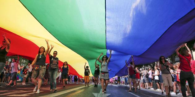 Varias personas portan una bandera gigante durante la manifestación del Orgullo de Valencia.