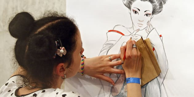 A girl draws during the 'Kyiv Comic Con' festival.