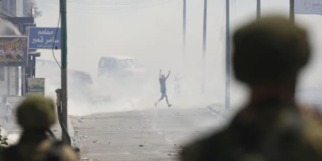 A Palestinian runs for cover from tear gas shot by Israeli soldiers during clashes in the West Bank city of Bethlehem, Friday, July 21, 2017 (AP Photo/Nasser Shiyoukhi)