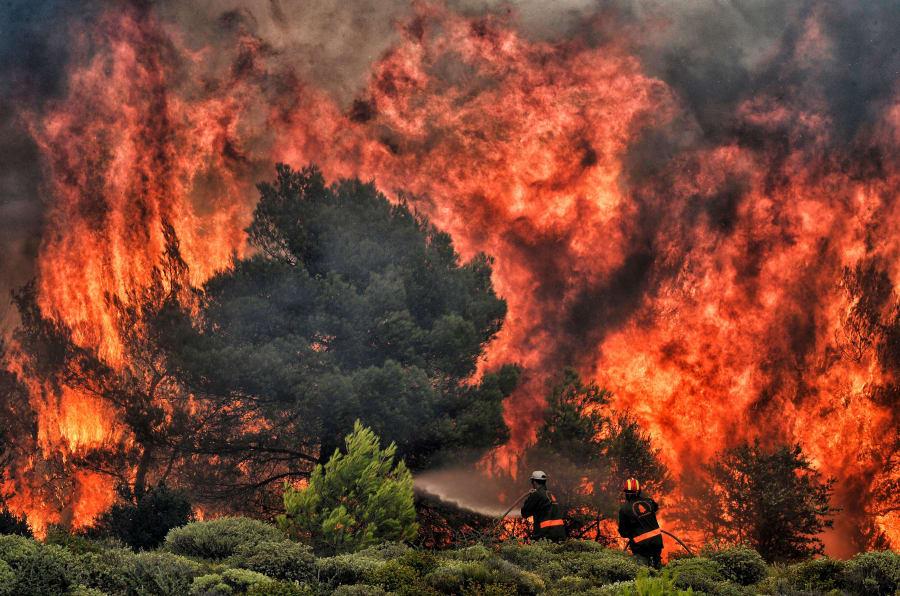 Bomberos tratan de controlar la columna de fuego en el poblado de Kineta, cerca de Atenas.
