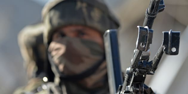 An Indian army soldier stands guard near the scene of an attack on a Indian Central Reserve Police Force (CRPF) convoy at Panthachowk on the outskirts of Srinagar.