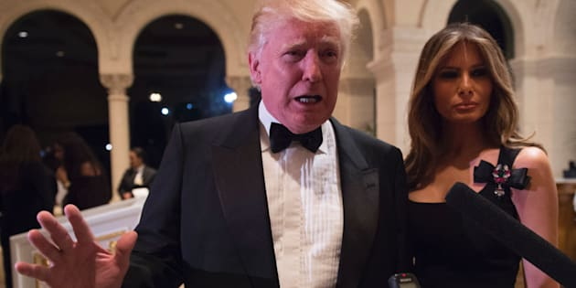 US President-elect Donald Trump answers questions from reporters accompanied by wife Melania for a New Year's Eve party December 31, 2016 at Mar-a-Lago in Palm Beach, Florida. / AFP / DON EMMERT        (Photo credit should read DON EMMERT/AFP/Getty Images)