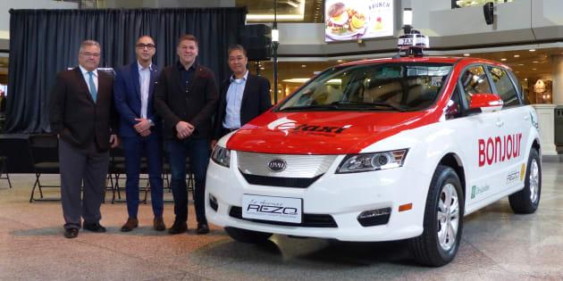 Le modèle e6 de BYD aux couleurs de Montréal. De gauche à droite sur la photo : M. Daniel Breton, ancien ministre de l'Environnement et expert-conseil en électrification des transports, M. Fabien Cuong, cofondateur de E-Taxi, M. Ted Dowling, vice-président de BYD Canada, et M. Yung Cuong, cofondateur de E-Taxi.