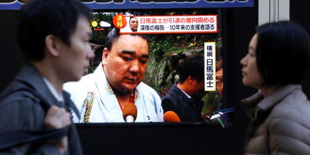 People walk past a street monitor showing Sumo grand champion Harumafuji, in Tokyo, Japan, November 29, 2017.  REUTERS/Toru Hanai