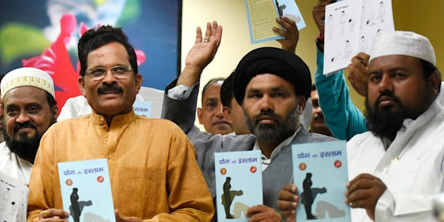 NEW DELHI, INDIA - JUNE 17: Minister of State for AYUSH, Shripad Naik (L) with other Muslims clerics release the book titled 'Yoga and Islam'; the booklet is compiled by the Muslim Rashtriya Manch (MRM), a wing of RSS, at Ayush Bhawan, on June 17, 2015 in New Delhi, India. The book also draws parallels between some yoga exercises and namaaz. (Photo by Vipin Kumar/Hindustan Times via Getty Images)