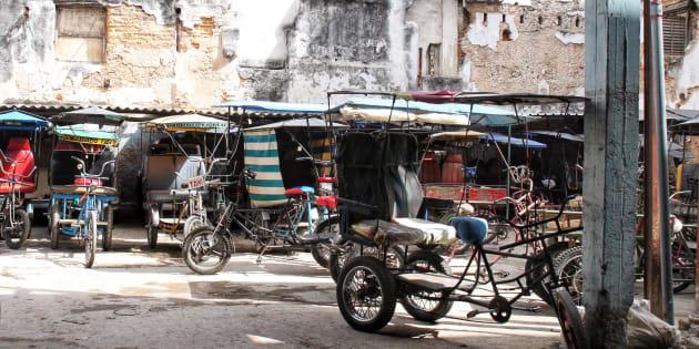 Stationnement de tricycles taxis. Les citadins de la Havane ont rarement un bout de terrain sécuritaire pour stationner leur engin. Les stationnements de l'état pallient à ce problème.