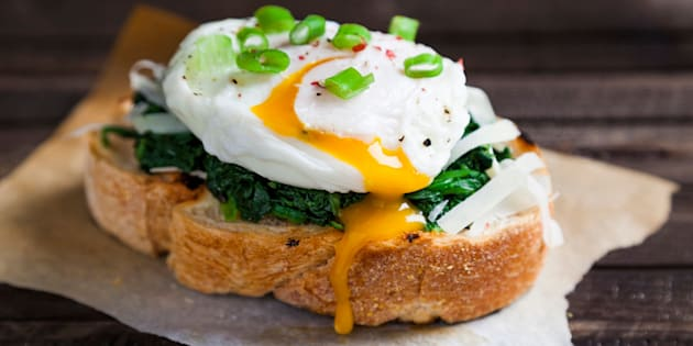 one portion of delicious fresh eggs benedict on crisp slices of toast grilled spinach flavored with pepper and Parmesan cheese onions ready to eat lying on the table rustic brown wood