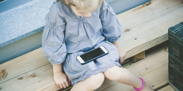 little girl watching something interesting on the mobile device.
