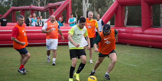 Minister for Health and Sport, Greg Hunt, (centre, in hat) plays against the Street Socceroos team at the Big Issue competition at parliament on Wednesday.