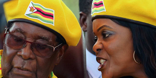 President Robert Mugabe listens to his wife Grace Mugabe at a rally of his ruling ZANU-PF party in Harare, Zimbabwe, November 8, 2017.