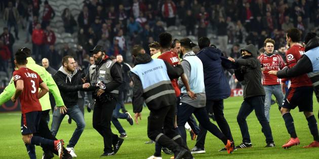 Les joueurs lillois mis en sécurité après l'envahissement de terrain par des dizaines de supporters.