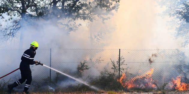 """Un pompier tente d'éteindre l'incendie d'Artigues, le 25 juillet, qui a connu une """"reprise importante"""" jeudi soir."""