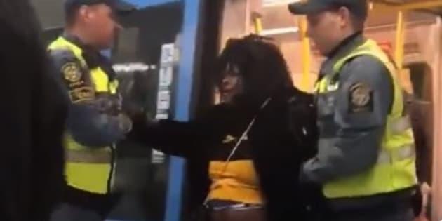 警備員によって地下鉄の電車から降ろされる女性