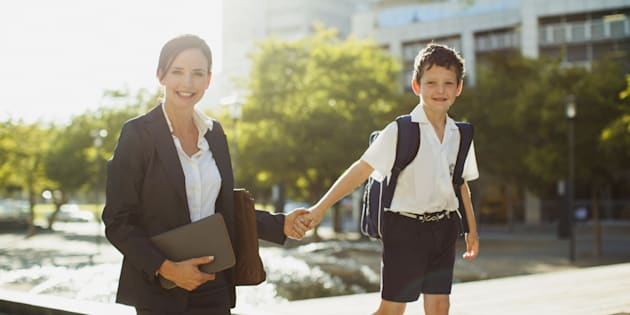 Smiling businesswoman walking with son outdoors