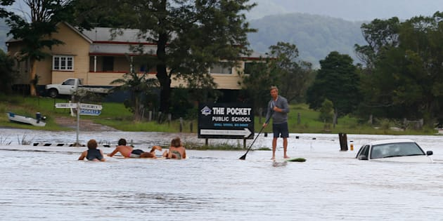 Locals paddle down the main street of Billinudgel in NSW.