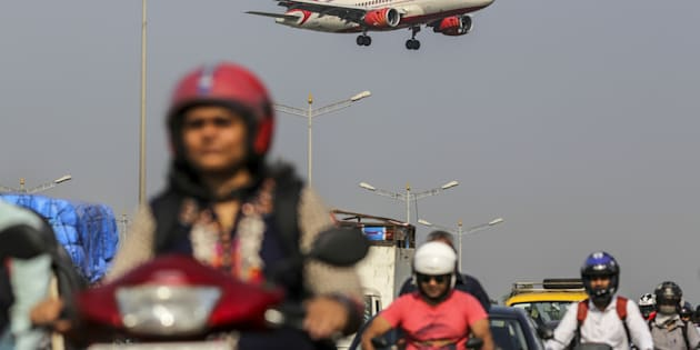 An Air India Ltd. aircraft passes over traffic as it prepares to land at Chhatrapati Shivaji International Airport in Mumbai, India, on Monday, Nov. 7, 2016.