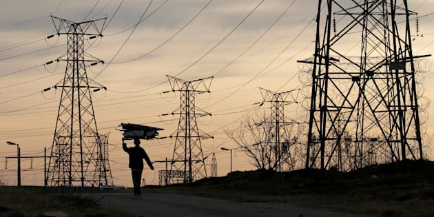 A woman carries fire wood on her head as she walks below state power utility ESKOM's elecricity pylons in Soweto, South Africa, August 8, 2016. Picture taken August 8, 2016. REUTERS/Siphiwe Sibeko/File Photo